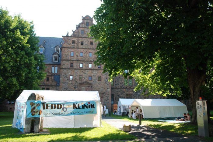 Willkommen! Die Teddyklinik findet einmal im Jahr vor dem Gießener Zeughaus statt. Neugierig auf einen Blick in die Zelte? Dann lass uns nun beginnen mit dem virtuellen Rundgang durch die Teddyklinik.